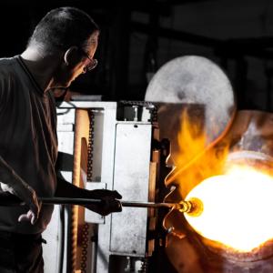 Glasmachermeister beim Aufblasen der Glaskugel
